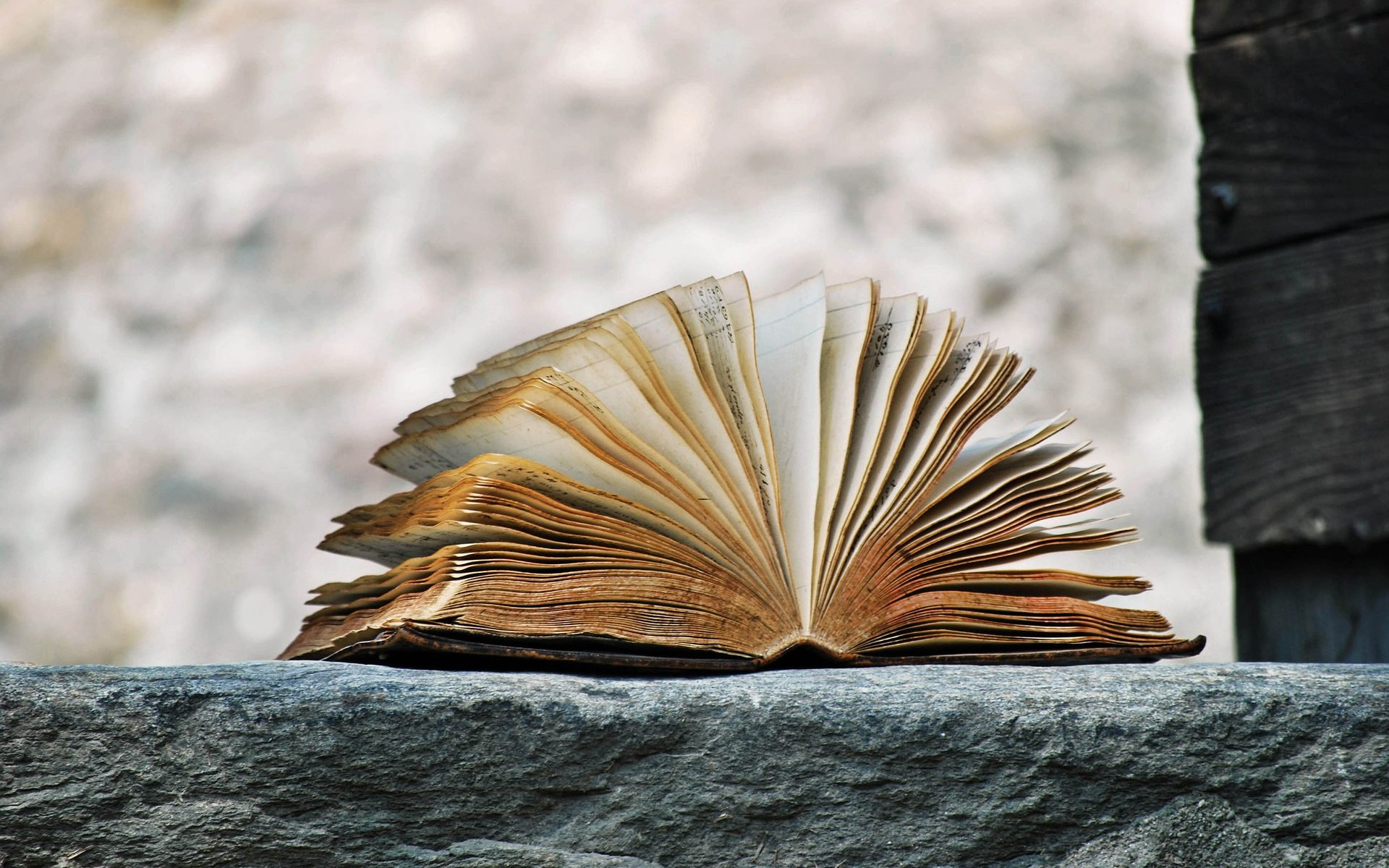 open old book on stone wall