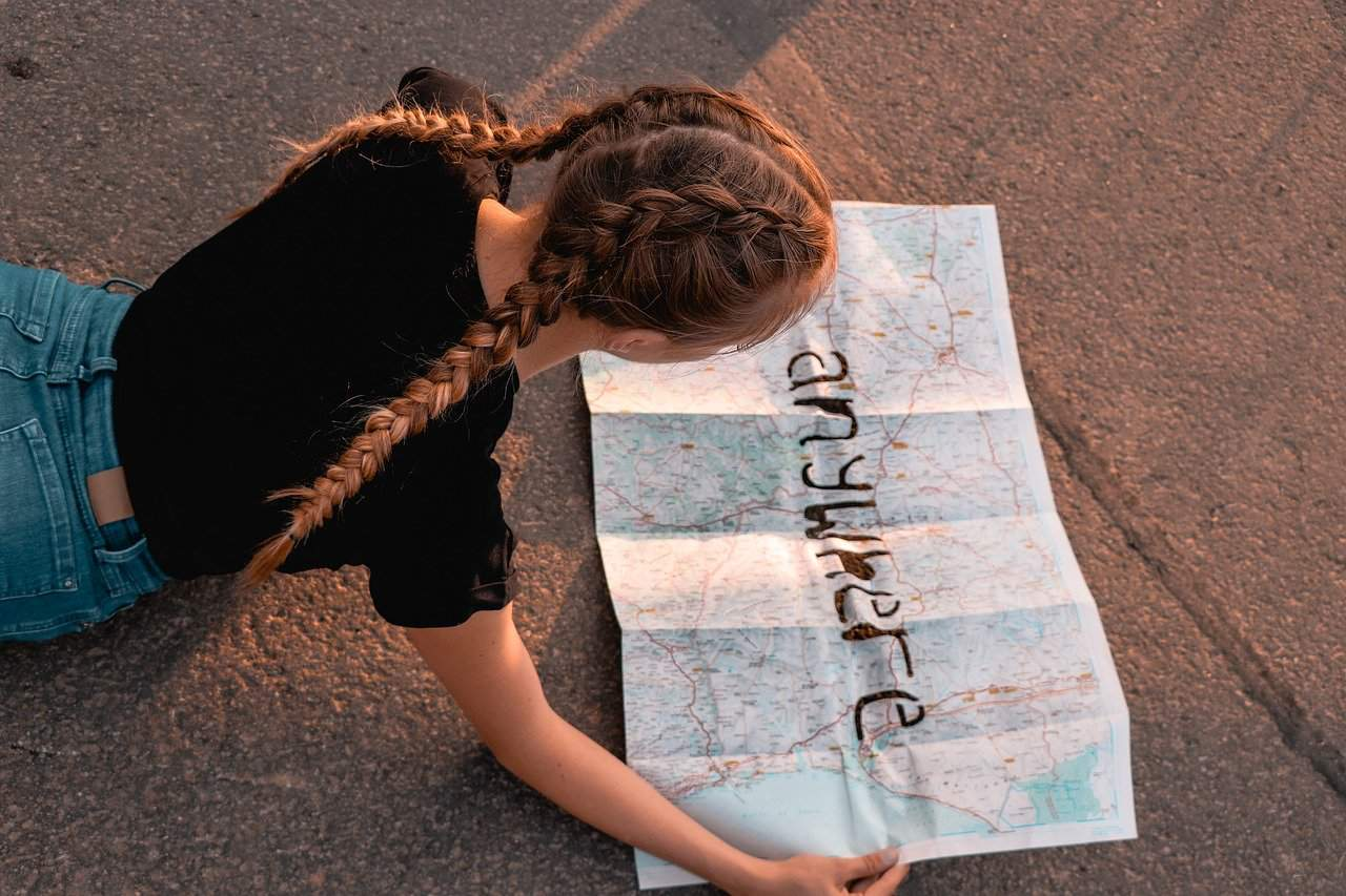 "girl with a map that has ""anywhere"" written across it"